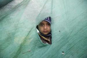 Un bambino guarda attraverso uno squarcio in una tenda montata per ospitare le persone rimaste senza casa dopo il terremoto - Katmandu, Nepal, 27 aprile 2015 (EPA/NARENDRA SHRESTHA)