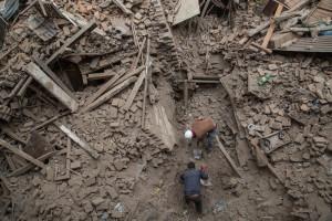Due persone al lavoro tra le macerie di alcuni palazzi crollati - Bhaktapur, Nepal, 26 aprile 2015 (Omar Havana/Getty Images)
